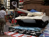 Shopper stands in front of a mock tank during an exhibition on Beijing's 1989 pro-democracy movement and its military crackdown, in Hong Kong