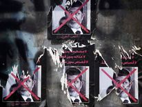 Torn posters of ousted Egyptian President Mohamed Mursi are seen on a wall at Tahrir Square in Cairo