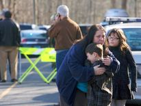 A young boy is comforted outside Sandy Hook Elementary School after a shooting in Newtown