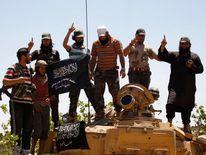 Islamist Syrian rebel group Jabhat al-Nusra members gesture while posing on a tank on Al-Khazan frontline