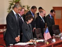 Barack Obama and South Korean President Park Geun-Hye bow their heads