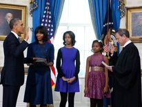 U.S President Barack Obama (L) takes the oath of office as first lady Michelle Obama holds the bible in the Blue Room of the White House in Washington