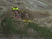 The boy's frightened face can be seen as the rescuer takes him towards the shore