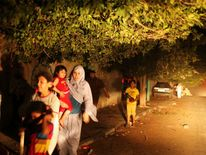 Palestinians flee their houses at scene of what witnesses said was Israeli air strike in Gaza City
