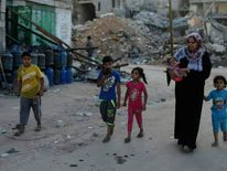Palestinians flee their house on foot in Beit Hanoun town in the northern Gaza Strip