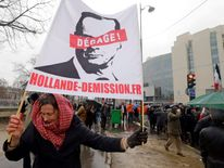"A demonstrator holds a banner which reads, ""Hollande Resign"" as several thousand people attend the ""Journee de la Colere"" (Day of Anger) march in protest of France's President Francois Hollande, in Paris"
