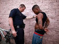 LAPD Officer Romero looks for gang tattoos on a man who was drinking alcohol in the street in south Los Angeles