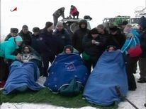 Still image taken from video shows NASA's Ford of the U.S. and Russian cosmonauts Novitskiy and Tarelkin wrapped in blankets after leaving the Russian Soyuz space capsule following its landing in the steppes of Kazakhstan, northeast of the town of Arkalyk