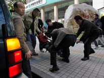 A protester is taken away by plainclothes police officers and placed in a jeep near the office of Southern Weekly newspaper in Guangzhou