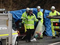 A policeman with a bag of items removed from the crashed car at the scene on the M6