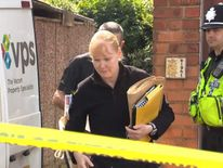 Police officers remove evidence from a suspect's home