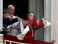 Pope Francis looks as a boy and a girl release two doves during the Angelus prayer in Saint Peter's square at the Vatican