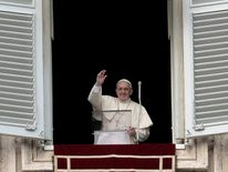 Pope Francis waves to the faithfuls gathered in St Peter's Square at the Vatican as he leads his Sunday Angelus prayer
