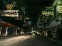 Lights off in the red light district of Patpong after the start of the curfew