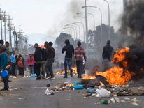 People walk past burning barricades of t