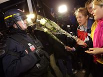 Demonstrators offer white roses to riot policemen during a protest over France's planned legalisation of same-sex marriage in Paris