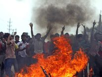 Protesters set fire to furniture from a police control room during a demo in Dhaka