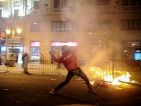 A protester throws stones at riot police officers at the end of a demonstration in Spain.