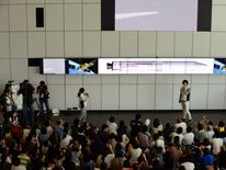 Guests gather to watch a projected live transmission image (top) of the launch of Japan's new solid-fuel Epsilon rocket carrying satellites from the Uchinoura Space Centre in Kagoshima, at the National Museum of Emerging Science and Innovation in Tokyo