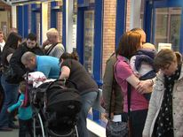 people queue at drop in centre for MMR vaccination