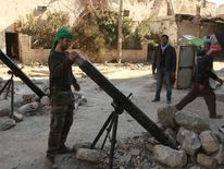 A Free Syrian Army fighter prepares to launch a mortar shell towards forces loyal to Syria's President Bashar al-Assad in Aleppo