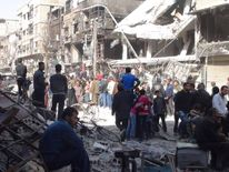 Palestinians wait to receive humanitarian aid distributed by the UN at al-Yarmouk camp