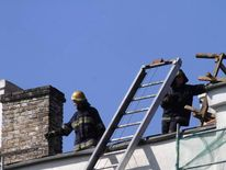 Firefighters inspect the roof of the Riga castle