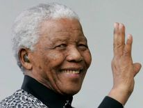 South Africa's former President Nelson Mandela waves as he arrives to attend the unveiling ceremony of a statue in his honour in London's Parliament Square