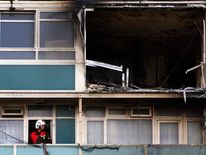 A fire officer surveys the damage at Lukanal House after six people died in a fire in Camberwell south London