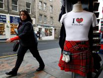 A woman walks past a tourist shop in the Royal Mile in Edinburgh, Scotland