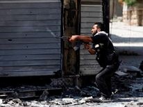 A Free Syrian Army fighter fires an AK-47 rifle in Aleppo August 15, 2012.
