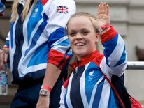Paralympic swimmer Ellie Simmonds waves during a parade of British Olympic and Paralympic athletes through London