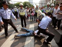 Policemen tackle a demonstrator on the ground during a protest near the Japanese consulate on the 81st anniversary of Japan's invasion of China, in Shanghai