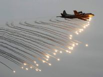 A Japanese Maritime Self-Defense Force P-3C patrol aircraft launches flares during a naval fleet review at Sagami Bay, off Yokosuka, south of Tokyo