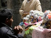 A man prays to decorated skulls during a 'Day of the Skulls' ceremony