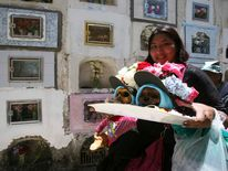 A woman carries decorated skulls during a 'Day of the Skulls' ceremony