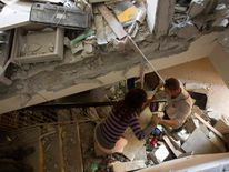Israelis survey the damage after a rocket hit their house in the southern city of Beersheba