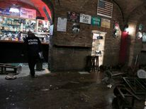 A policeman stands in a damaged pub after a fight in downtown Rome