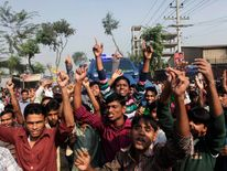 Workers shout slogans as they protest against the death of their colleagues after a devastating fire in a garment factory which killed more than 100 people, in Savar