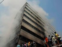 Fire fighters try to control a fire as smoke engulfs an 11-storey garment factory building in the suburb of Uttara in Dhaka