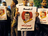 "Pro-Morsi supporters hold banners reading ""I support the President's decisions"", during a march in Cairo"