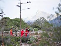 Civil Protection personnel and soldiers at the perimeter of the crash site of a plane with Mexican-American singer Jenni Rivera on board