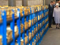 Britain's Queen Elizabeth and her husband Prince Philip  tour a gold vault during a visit to the Bank of England in the City of London