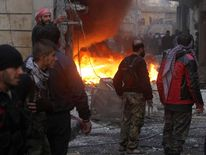 Free Syrian Army fighters stand near a fire after shelling by forces loyal to Syria's President Bashar al-Assad, at al-Ansari area in Aleppo