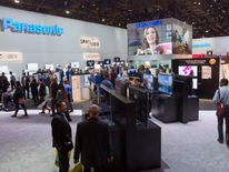 CES attendees look over television sets at the Panasonic booth