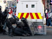 Police officers help an injured colleague during rioting in East Belfast,