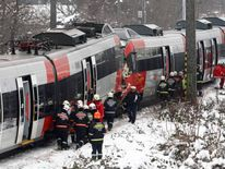 Austrian rescue personnel stand in front of two demolished S45 trains after a train crash in Vienna