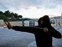A Palestinian protester uses a slingshot to hurl a stone at Israeli security forces during clashes in Bethlehem