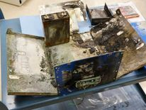 NTSB investigators display the exterior case of a thermal-damaged lithium ion battery, as a part of their ongoing investigation into why the battery caught fire in a Japan Airlines' 787 parked at Boston Logan International Airport January 7, at their labs