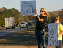 Sherry Johnson Parker and her daughter Olivia Parker, from New Hope, hold signs along Highway 231 asking drivers to pray for Ethan, a 5-year-old boy taken hostage five days ago, after a bus driver was shot and killed near Midland City